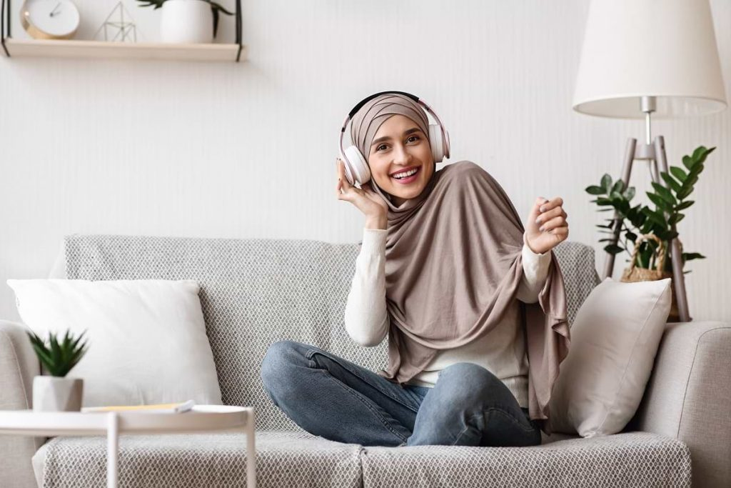 arab-girl-sitting-on-sofa-and-listening-music-with-GHVRU2F (1)